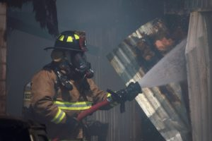 A fireman sprays a hose with a walkie on his shoulder that requires a distributed antenna system